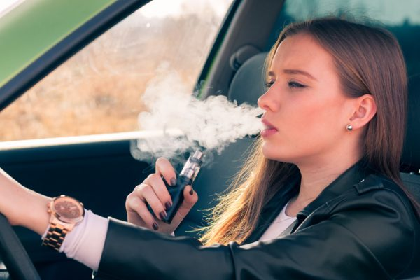 Woman Vaping behind the wheel